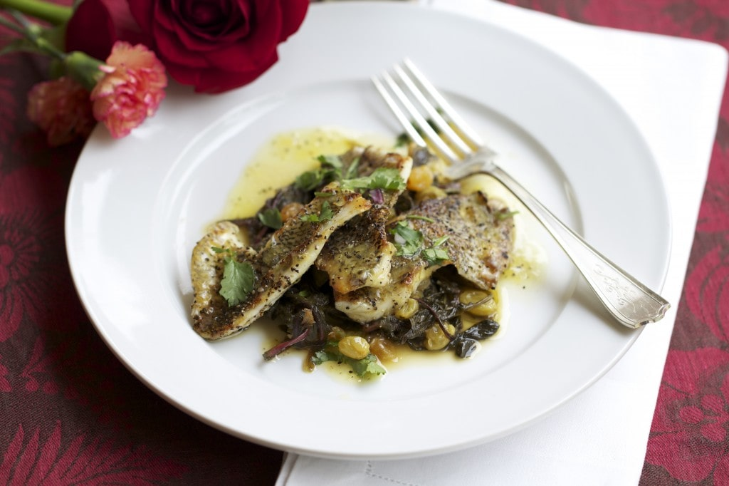 bream fillets with dandelion greens on white plate