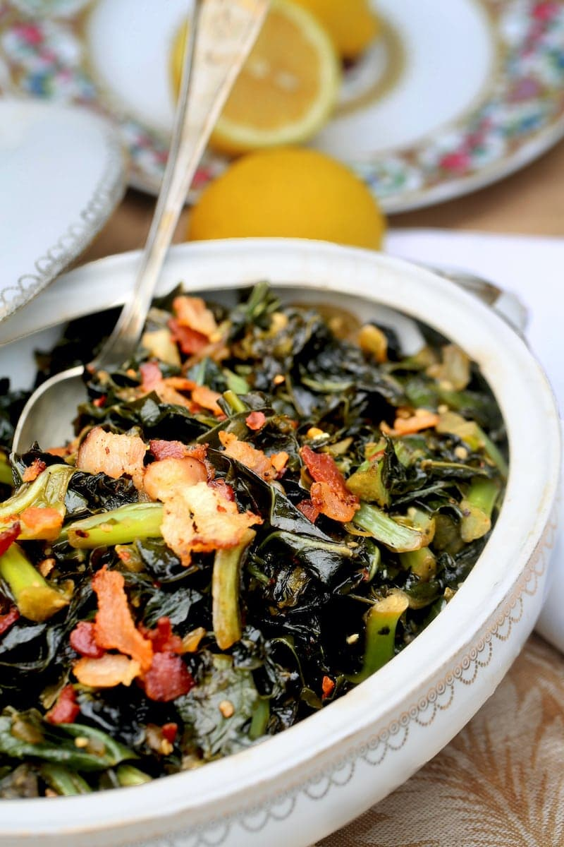 Collard greens with bacon on top in an antique white casserole dish with china plates in the background