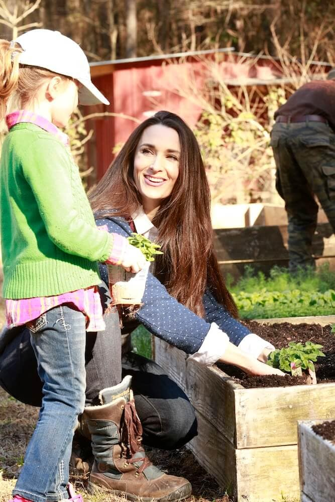 Stacy teaching her daughter how to garden