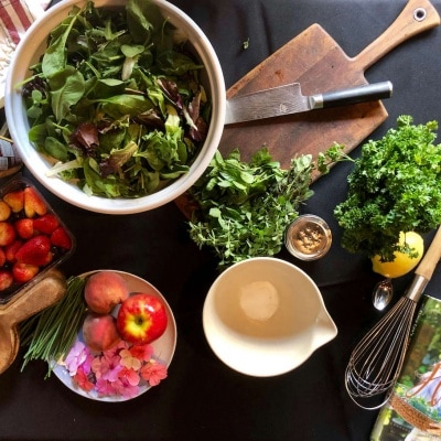 Table setting for herb salad with edible flowers fruits nuts and simple vinaigrette
