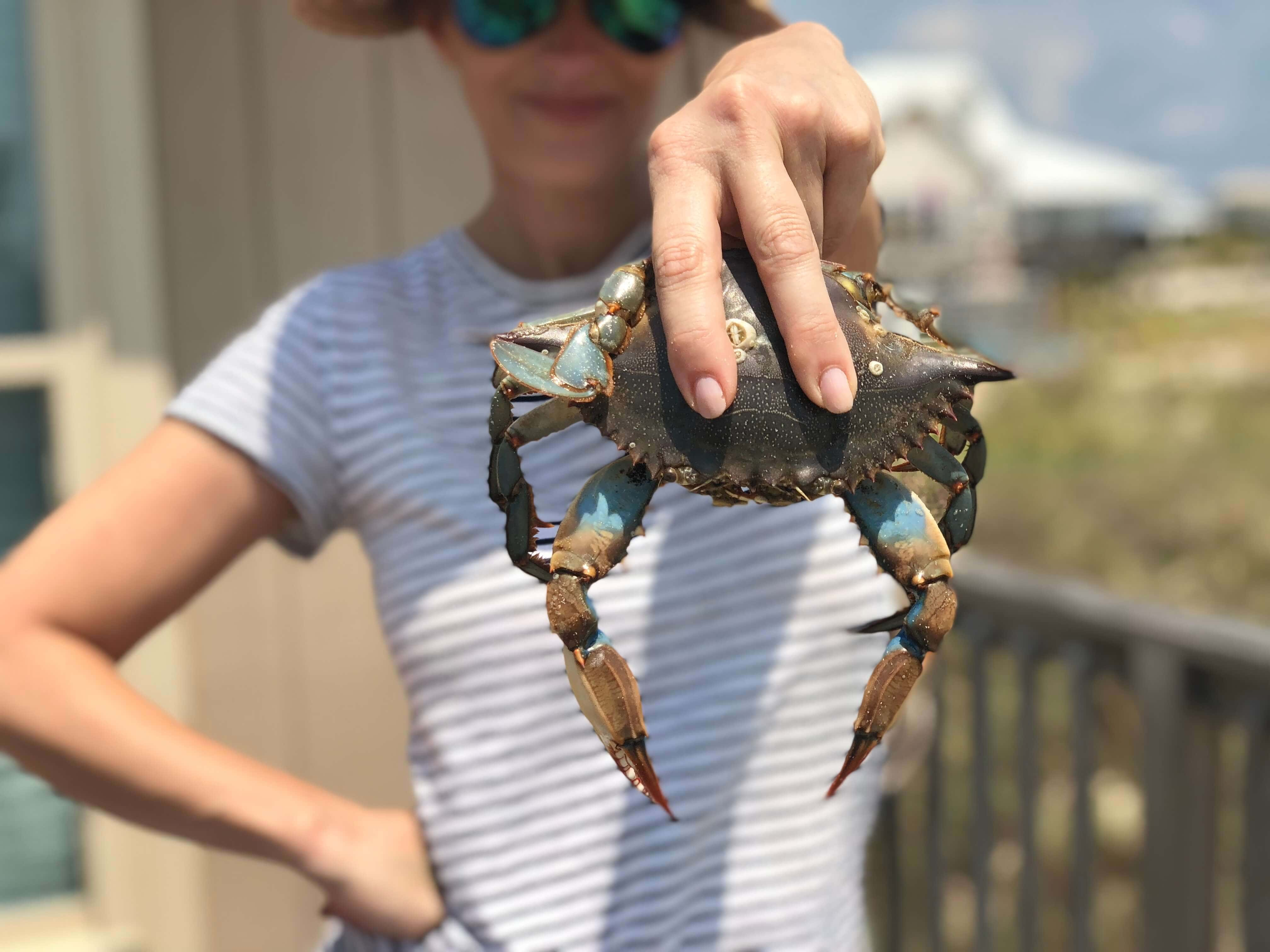 Stacy Lyn emphatically holding up a freshly caught crab
