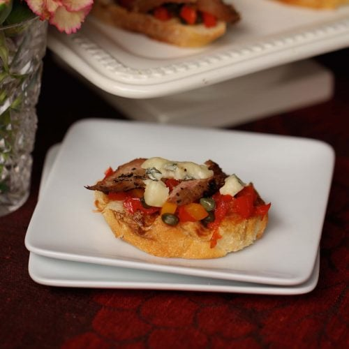 Bruschetta hors d'ouvres with venison, peppers, tomatoes, blue chees and olive oil