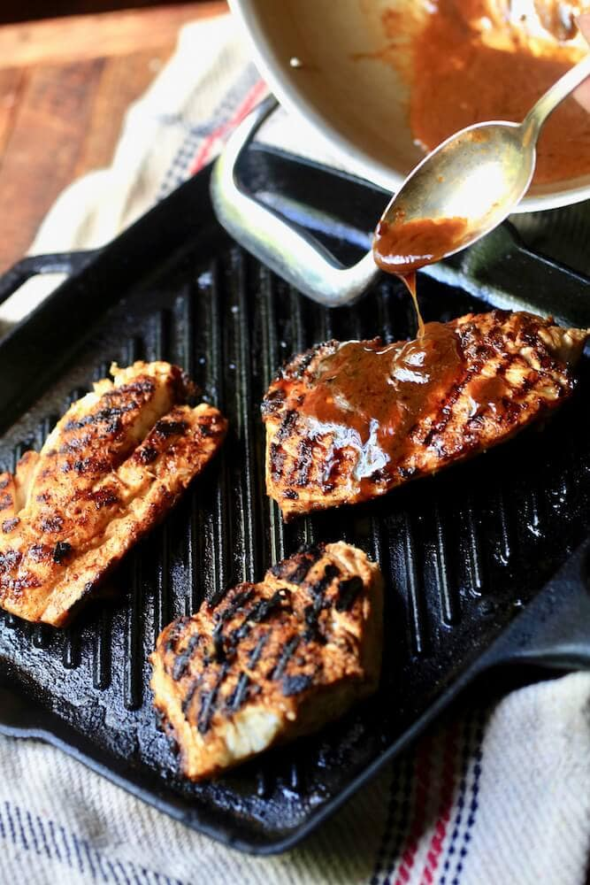 A picture of a spoon drizzling comeback sauce on Stacy Lyn Harris's seasoned Blackened Redfish dish
