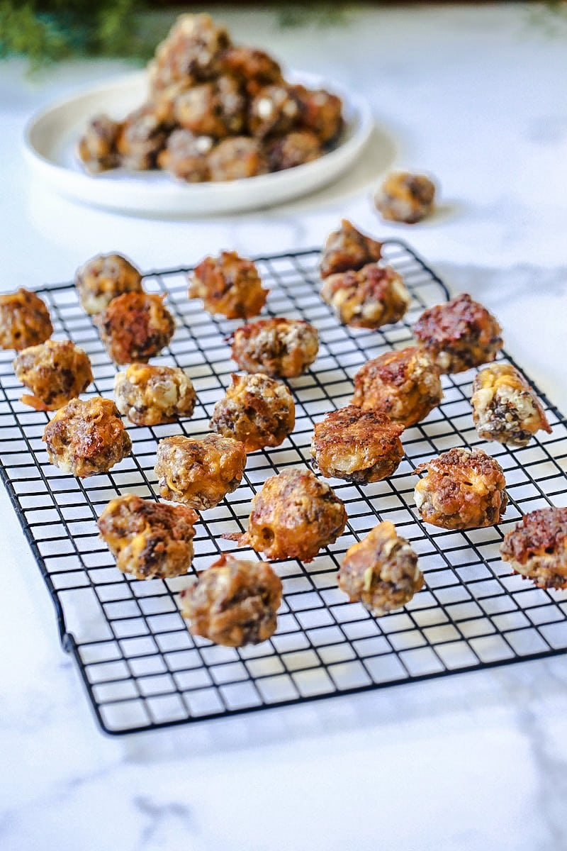 Sausage Balls on a cooling rack on white marble with a plate of sausage balls behind it.