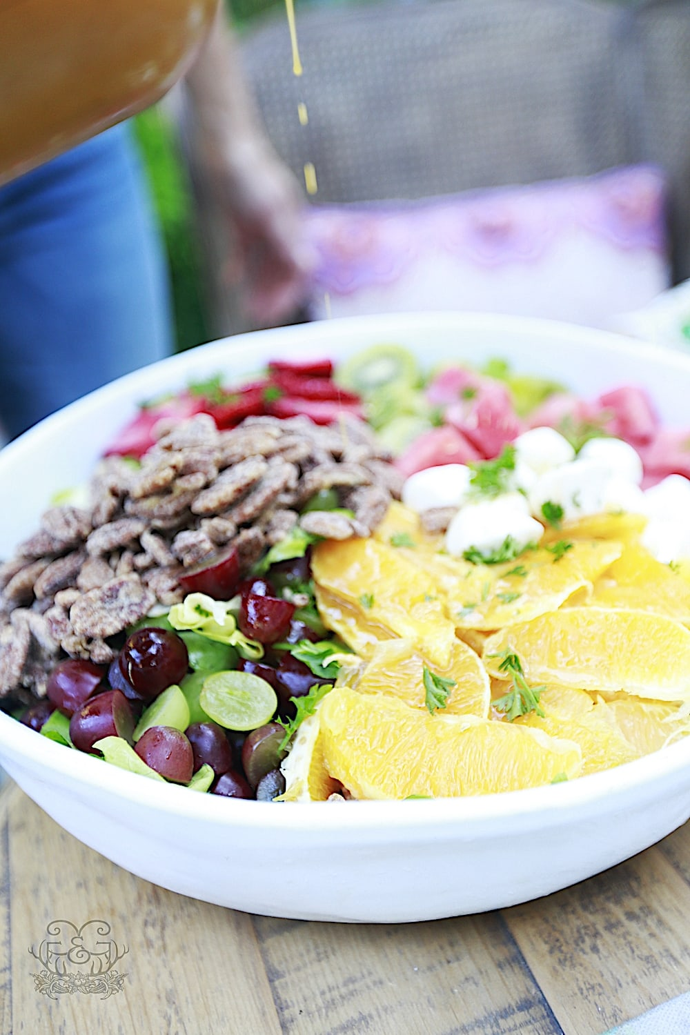 Salad in large white bowl filled with lettuce, pecans, orange slices, strawberries, grapes, strawberries, mozzarella on a table