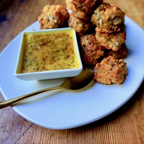 Sausage balls served with mustard red pepper jelly sauce on white plate