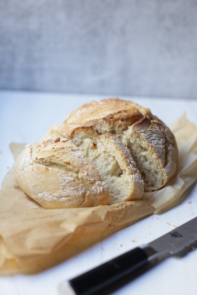Artisan Bread on parchment with knife sitting beside it. on white and gray background.