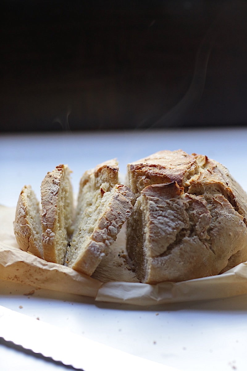 Artisan Crusty Bread on parchment paper on white background with black background with steam rising from the bread