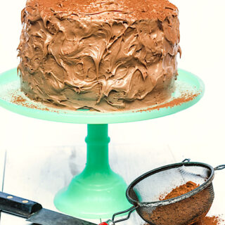4 layer cappuccino cake on green cake stand with knife in front of it along with cocoa powder in a sieve