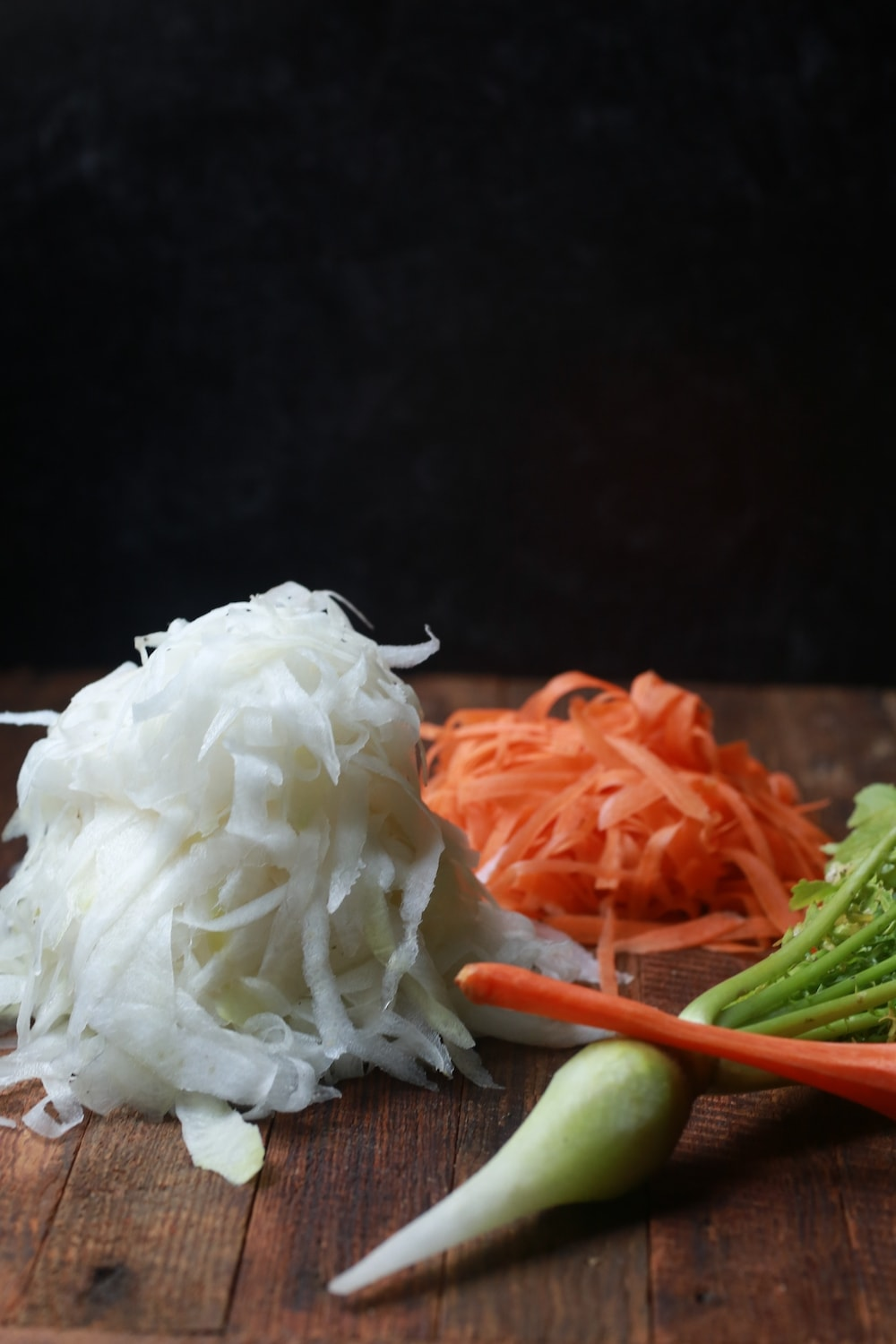 Peeled Daikon Radishes and Carrots on wood with a black background