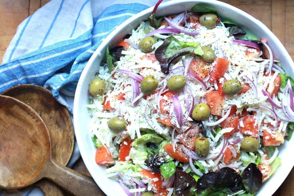 closeup of tossed Italian salad recipe with wooden utensils