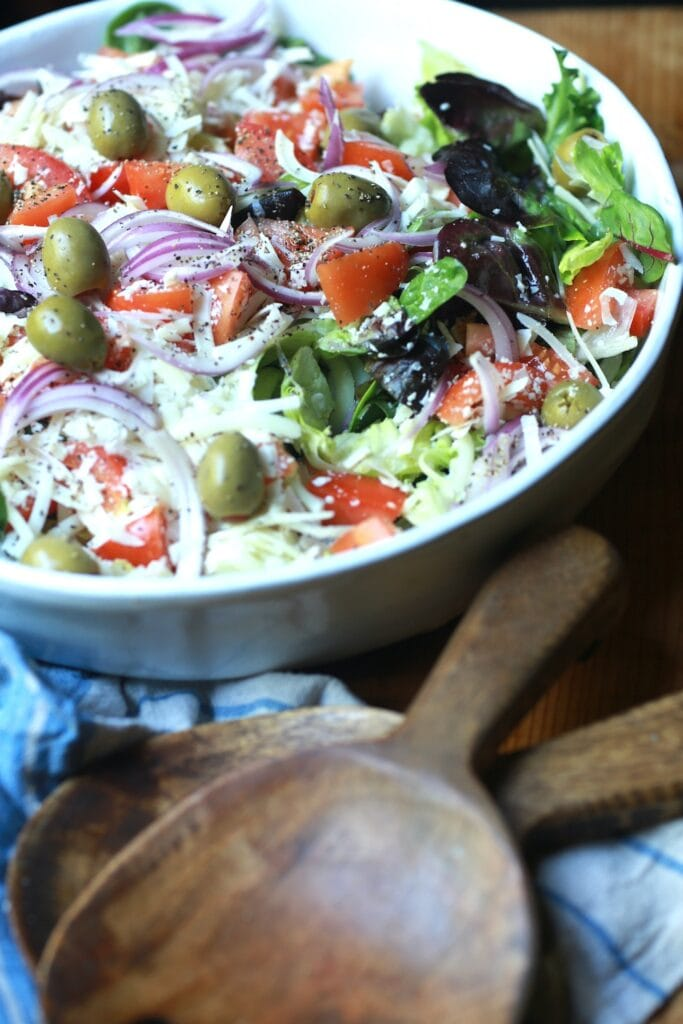 Up close view of fresh Italian salad tossed in white bowl.