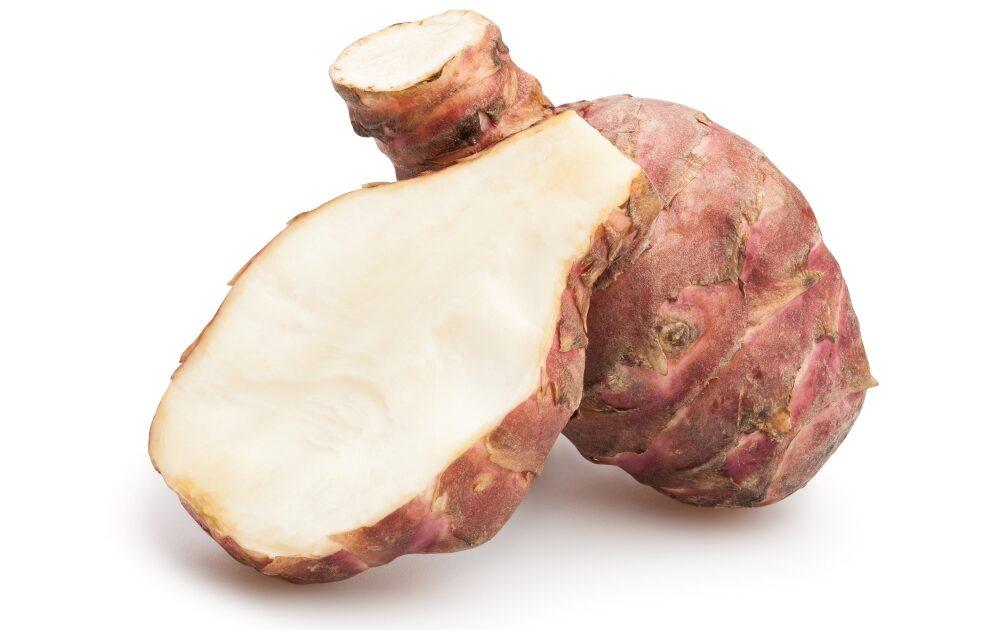 sliced Jerusalem artichoke in front of whole tuber