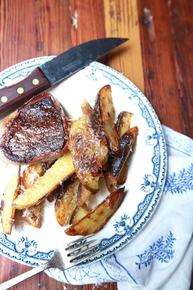 closeup of potato wedge fries on decorative plate with steak