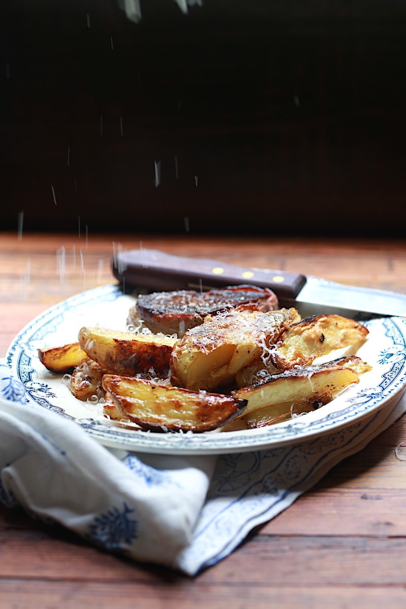 Plate with oven baked wedge fries alongside steak with parmesan