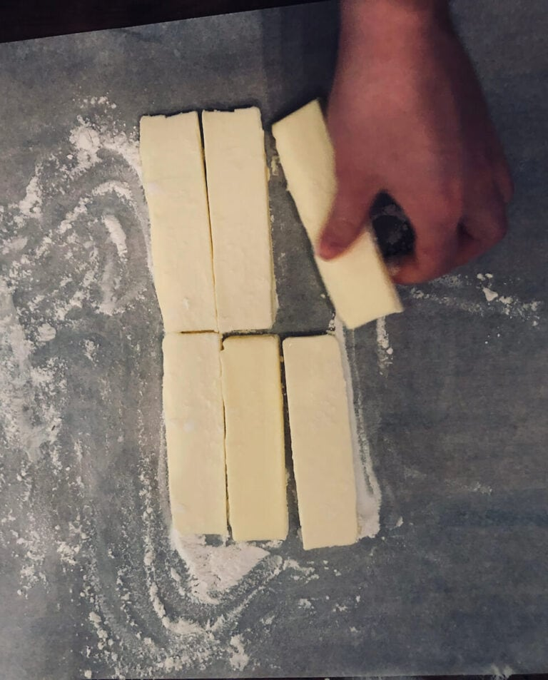 Sprinkle a little flour over the butter and and cover with another piece of parchment.